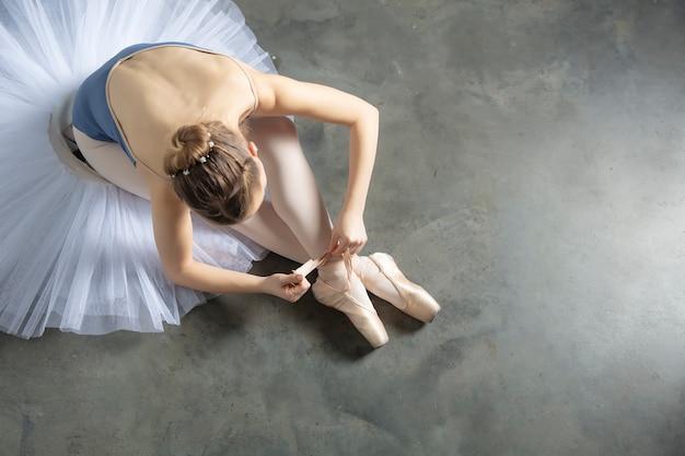 Vista dall'alto al ballerino di danza classica legando le pantofole intorno alla caviglia