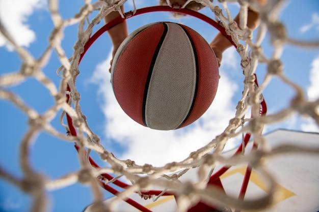 Vista dall'alto del gioco di allenamento per bambini di basket vista della palla volante al canestro dal bambino in alto gioca a basket
