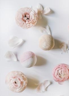 Vista dall'alto di bombe da bagno e teneri fiori su sfondo chiaro