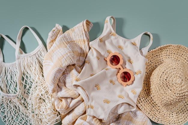 Vista dall'alto degli accessori estivi da spiaggia per bambini. costume da bagno alla moda e cappello per bambini. lay piatto