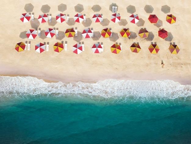 Vista dall'alto della spiaggia con ombrelloni e lettini sulla sabbia. l'uomo sulla spiaggia vicino all'acqua prende il sole al sole del mattino.