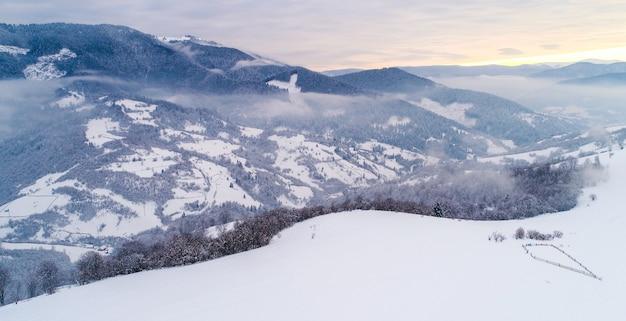 Vista dall'alto di un bellissimo paesaggio affascinante di montagne innevate e colline con alberi e nebbia in una fredda giornata invernale nuvolosa