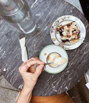 Vista dall'alto di un bellissimo tavolo con piatti vintage, mano femminile con una tazza di caffè e una deliziosa torta. bello e gustoso concetto di cibo.
