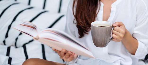 Vista dall'alto di un libro di lettura bella donna e bere caffè caldo in un letto bianco accogliente a casa