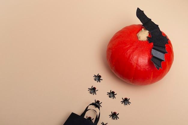 Vista dall'alto su un pacchetto nero sfondo beige con mosche, zucca e pipistrelli. primo piano di una festa di halloween. disposizione dell'invito. banner