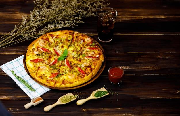 Vista dall'alto di una grande ciotola di gustosa pizza calda ai frutti di mare servita su un tavolo marrone con condimento, bicchiere di salsa di pomodoro, tovaglie e decorata da fiori secchi come cibo tradizionale italiano di lusso per un pasto classico