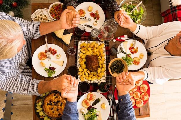 Vista dall'alto e dall'alto su un grande tavolo di legno pieno di cibo come pollo e un gruppo di persone che mangiano e prendono cibo dal centro del tavolo il giorno di natale