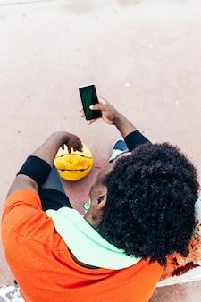Vista dall'alto di un ragazzo afro nero utilizzando il suo telefono cellulare sul campo da basket. tecnologia e sport di concetto.