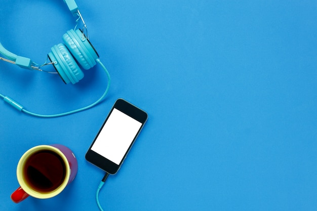 Vista superiore caffè nero, telefono cellulare e cuffie su sfondo blu con spazio di copia.