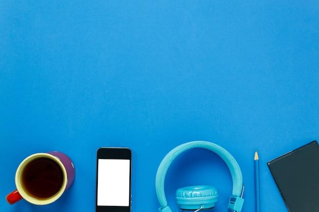 Vista superiore caffè nero, telefono cellulare, matita, carta nota e cuffie su sfondo blu con copia spazio.