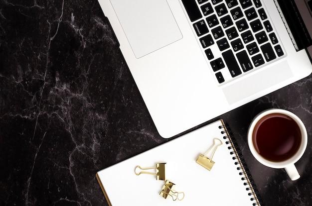 Vista dall'alto sul desktop nero con laptop, notebook, tazza di tè
