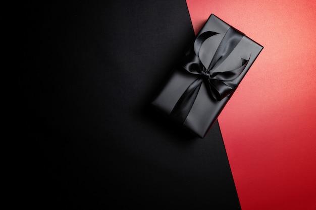 Vista dall'alto della confezione regalo nera con nastri neri isolati su rosso e nero