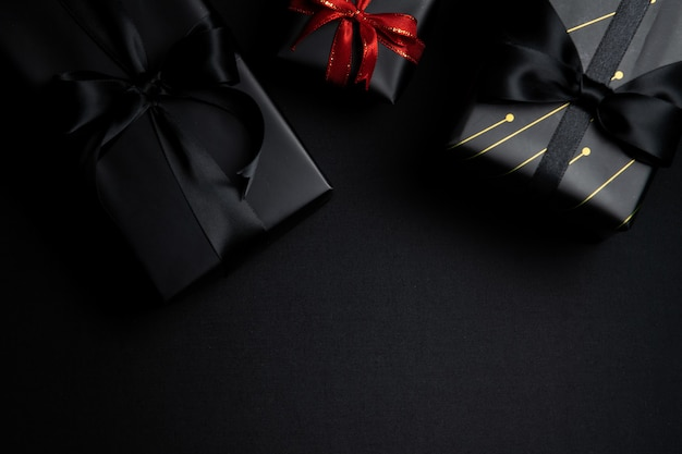 Vista dall'alto della confezione regalo nera con nastri rossi e neri isolati sul nero