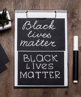 Vista dall'alto delle carte di materia di vita nera con appunti e penna