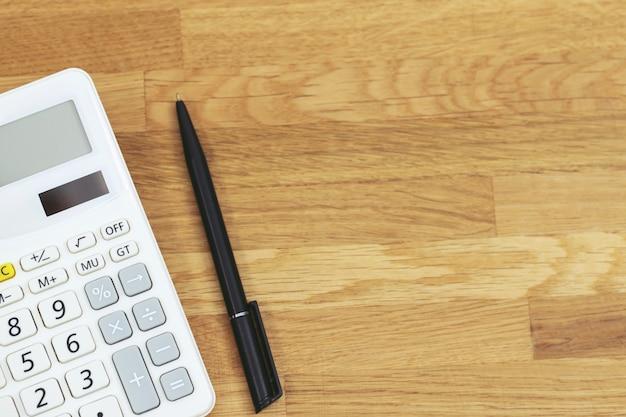Vista superiore della penna nera con la calcolatrice sul tavolo di fondo in legno tavolo scrivania vivido per affari con spazio vuoto copia, matematica, costo, tasse o calcolo di investimento