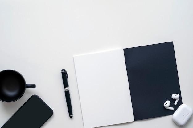 Taccuino, tazza, penna, auricolare e smartphone in bianco e nero con vista dall'alto su sfondo bianco.
