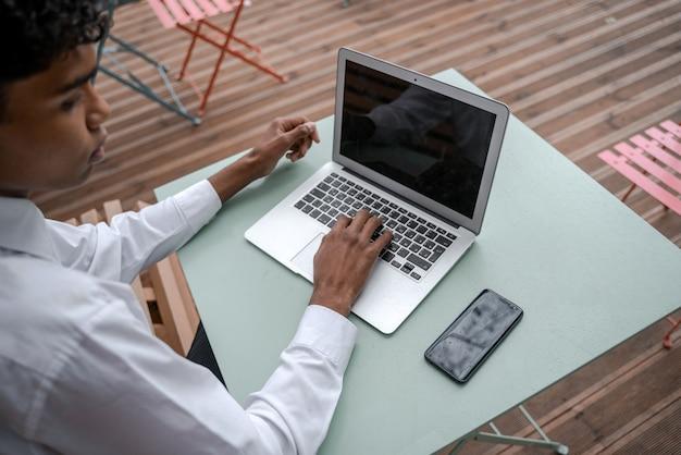 Vista dall'alto del posto di lavoro di un giovane nero. smartphone e laptop in terrazza. lavoro fuori dall'ufficio, lavoro a distanza o concetto di studio.