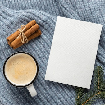 Vista dall'alto della scheda in bianco sul maglione con una tazza di caffè e bastoncini di cannella