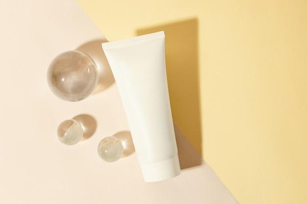 Vista dall'alto del tubo cosmetico vuoto su sfondo pastello sfere di vetro vicino al concetto di pulizia