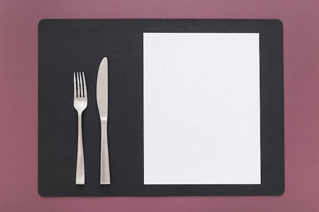 Vista dall'alto di carta menu vuoto con coltello e forchetta