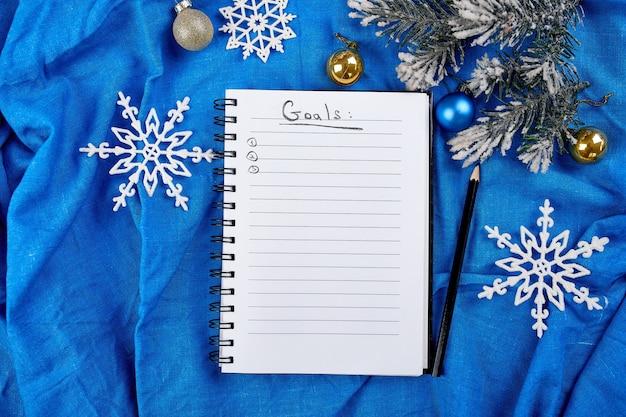 Vista dall'alto del taccuino vuoto per le risoluzioni degli obiettivi e decorazioni natalizie su lino tessile blu