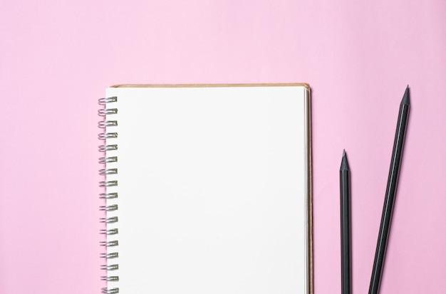 Vista superiore della carta e della matita del taccuino in bianco su fondo rosa, attrezzature per ufficio, scuola stazionaria e concetto di istruzione