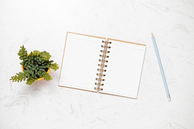Taccuino e matita in bianco di vista superiore sul fondo della tavola di marmo nel posto di lavoro dell'ufficio.