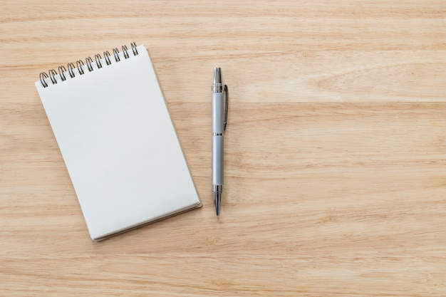 Vista superiore del taccuino in bianco con la penna e luce naturale sulla tavola di legno.