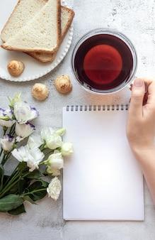 Vista dall'alto di un foglio di blocco note vuoto e la mano della donna nell'impostazione della colazione