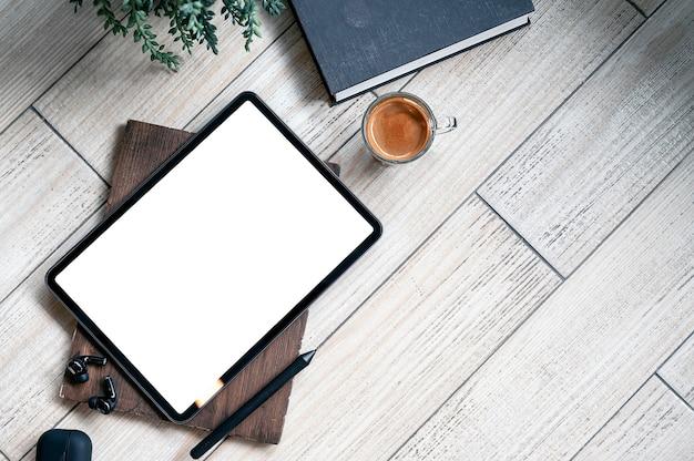 Tablet, gadget, libro e tazza di caffè con schermo vuoto vista dall'alto sul tavolo di legno con spazio per le copie.