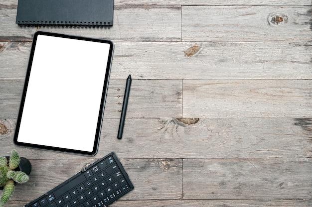 Tavoletta, penna, tastiera e taccuino dello schermo in bianco di vista superiore sul fondo della tavola di legno.