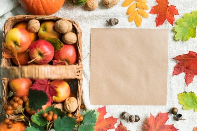 Vista dall'alto del foglio di carta bianco tra foglie autunnali, ghiande, noci e mele mature che possono essere utilizzate come