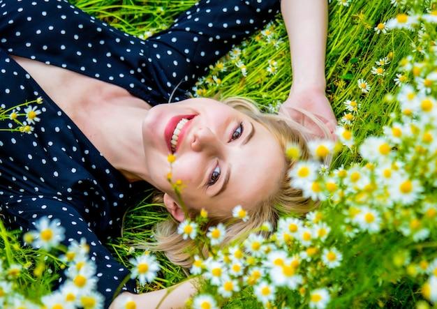 Vista dall'alto della donna bionda in abito nero sdraiato sul prato di fiori di camomilla