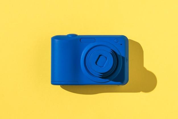Vista dall'alto di una telecamera blu su sfondo giallo e rosa. attrezzatura elegante per riprese di foto e video.