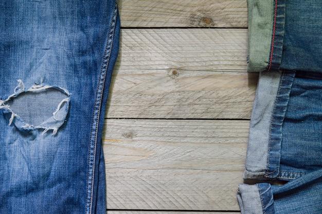La vista superiore dei jeans blu del denim ha sistemato su fondo di legno. concetto di abbigliamento di bellezza e moda