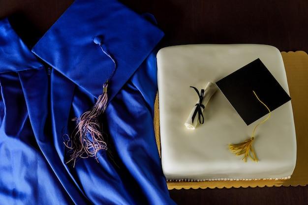 Vista dall'alto dell'abito da laurea blu e berretto con torta per la fine della scuola.