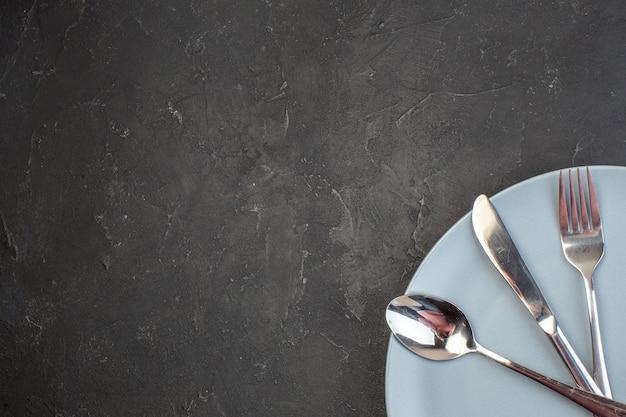 Piatto blu vista dall'alto con forchetta e coltello sulla superficie scura