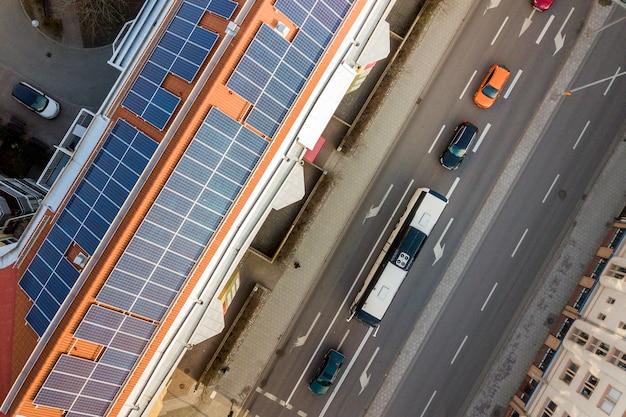 Vista superiore del sistema fotovoltaico solare blu dei pannelli fotovoltaici sulla cima del tetto dell'alta costruzione di appartamento il giorno soleggiato. concetto di produzione di energia verde ecologica rinnovabile. Foto Premium