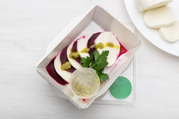 Vista dall'alto di barbabietole bollite con fette di formaggio bianco si trovano in una scatola da pranzo bianca con salsa di panna acida e prezzemolo su un tavolo bianco accanto al formaggio di capra. concetto di spuntino proteico.