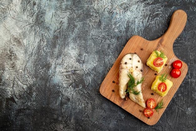 Vista dall'alto del pasto di grano saraceno di pesce bollito servito con formaggio verde di pomodori sul tagliere di legno sulla superficie del ghiaccio
