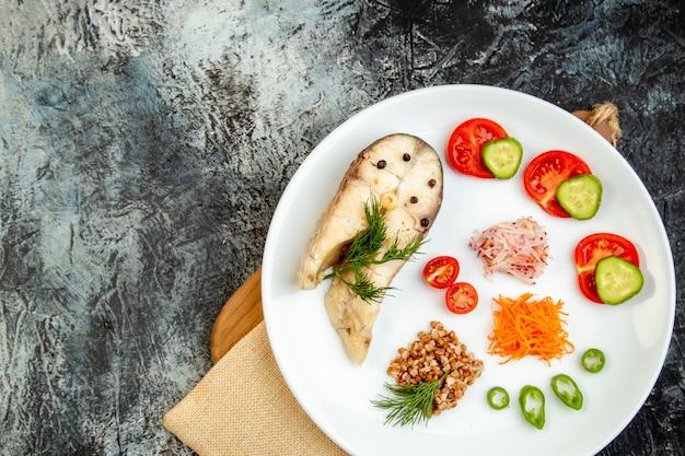 Vista dall'alto del pasto di grano saraceno di pesce bollito servito con verdure verdi su un piatto bianco su asciugamano nudo sul tagliere di legno sulla superficie del ghiaccio