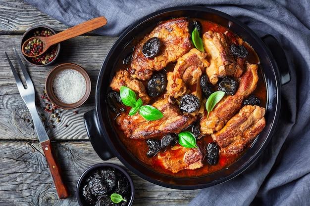 Vista dall'alto su costolette di maiale con osso brasate con prugne, brodo, cipolla e aglio, decorate con basilico fresco, servite su una teglia nera su un tavolo di legno rustico con ingredienti