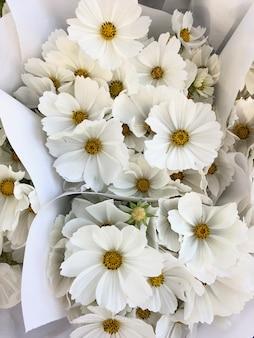 Vista dall'alto su mazzi di bellissimi fiori bianchi carini in carta da regalo bianca. concetto di fiori. concetto di sfondo.