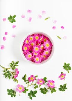Vista dall'alto della ciotola con petali rosa selvatici sulla ciotola di legno bianca su bianco