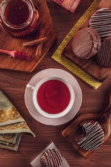 Vista dall'alto del brasiliano biscotto al miele ricoperto di cioccolato sul tavolo di legno con una tazza di tè in porcellana, miele delle api e cannella - pã £ o de mel