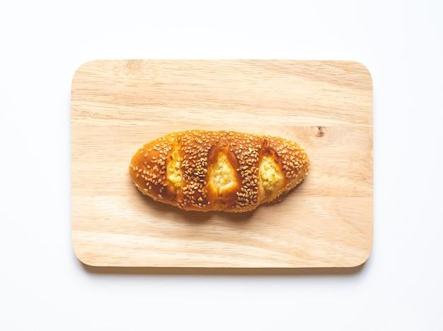 Vista dall'alto di pane e prodotti da forno con tagliere su sfondo di colore bianco.