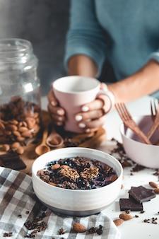 Vista dall'alto del tavolo della colazione con caffè, muesli, noci, frutti di bosco e latte