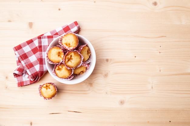Vista dall'alto della colazione con muffin e panno rosso sul tavolo di legno con spazio di copia