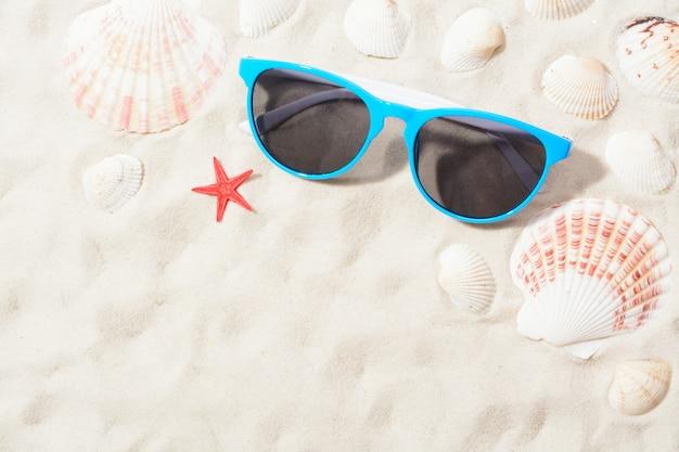 Vista dall'alto di occhiali da sole luminosi disposti con varie conchiglie sulla sabbia