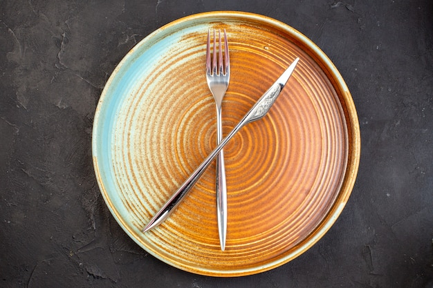 Vista dall'alto grande vassoio marrone con forchetta e coltello piatto su superficie scura